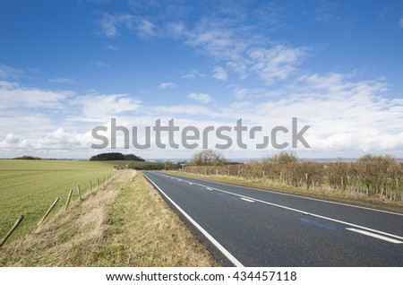 Empty tarmac road on a cold but sunny winter day with a blue sky and fields in Hampshire, England, United Kingdom.