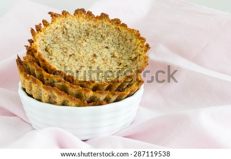 Empty tartlet in a white bowl, creased table cloth in the background - stock photo