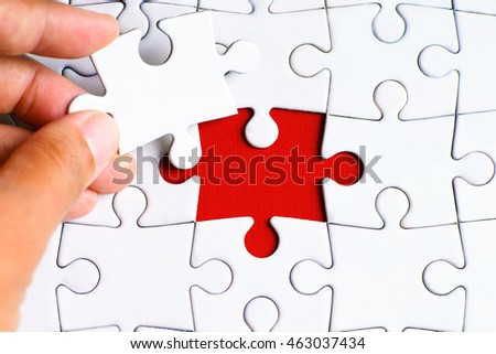 Empty text on missing puzzle with a hand hold a piece of puzzle want to complete it - business and finance concept