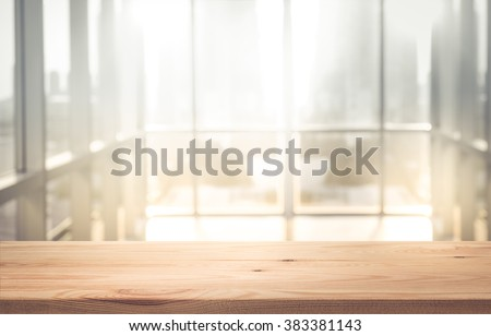 Empty the top of wood table with blur sunlight in window wall building background.for product display and presentation