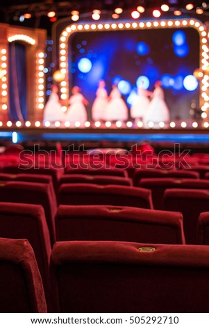 empty theater chairs and blurred stage lights
