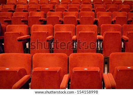 Empty theatre seats; tiered, empty red velvet seating  - stock photo