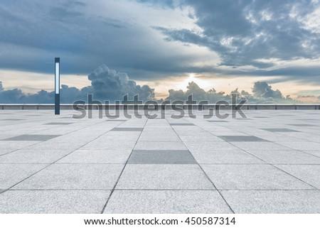 empty tiled floor against cloudy sky - stock photo