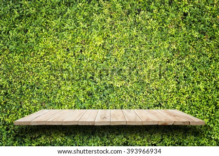 Empty top of wooden shelves and green pattern wall background. For product display