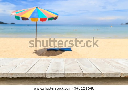 Empty top of wooden table and view of tropical beach background. For product display