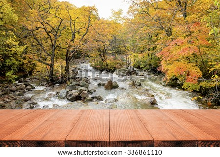 Empty top of wooden table or counter on background of Red Maple Color Leaf Fall Foliage Autumn Colors of  River Prefecture Japan. For product display,can be used for montage or display your products - stock photo