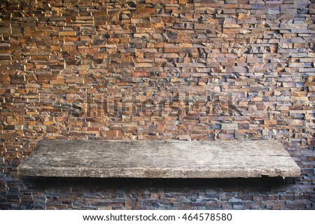 Empty top old wooden shelves on brick background.