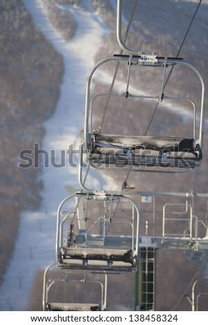 Empty triple chair lift with a ski mountain in the background, Stowe, Vermont, USA - stock photo