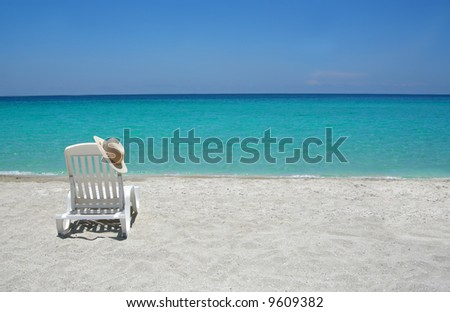 Empty tropical beach chairs on sand at shoreline in the Caribbean