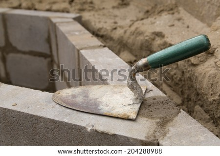 Empty trowel on a constructed wall outdoors - stock photo