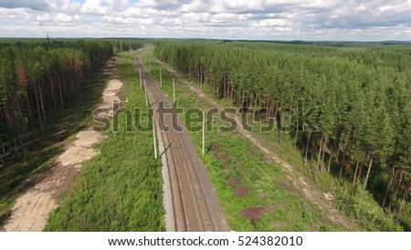 Empty two lines electric rail road in evergreen woods of Karelia, Russia. Aerial view