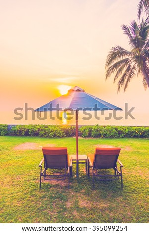 Empty umbrella and chair on the beach at Twilight Times - Vintage Filter