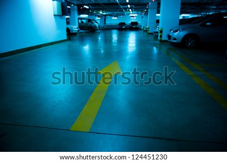 Empty underground parking garage at night - stock photo