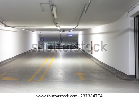 Empty underground parking lot area with lights - stock photo