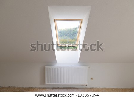 Empty unfinished new room with mansard window - stock photo