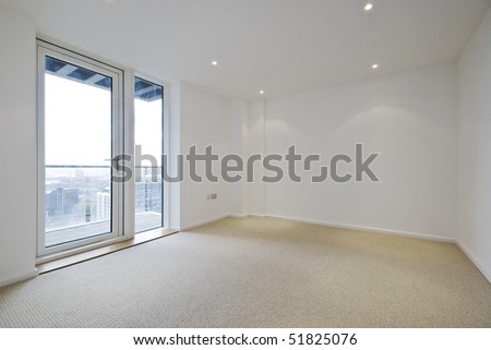 empty unfurnished room with beige carpet floor and balcony access - stock photo