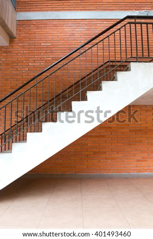 Empty university or hospital building stairway in front of a red brick wall wall - stock photo