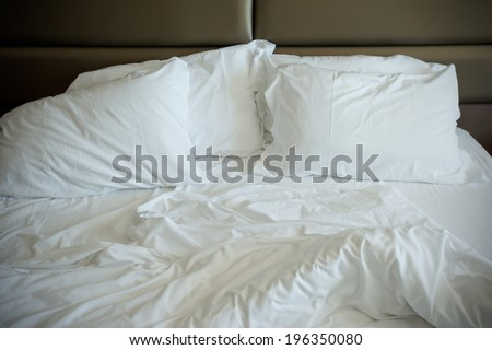 Empty unmade bed in a modern bedroom - stock photo