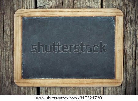 Empty vintage blackboard with wooden frame on a wooden backgroun - stock photo