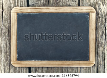 Empty vintage blackboard with wooden frame on a wooden background - stock photo