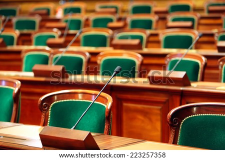 Empty vintage congress hall with seats and microphones. - stock photo