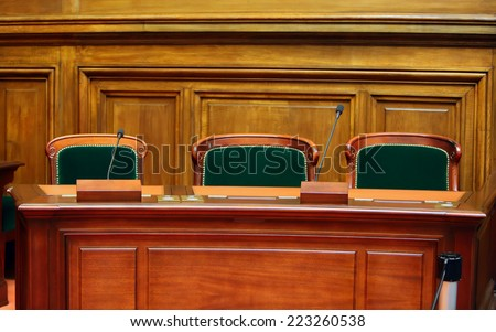 Empty vintage court's room with table,chairs and microphones. - stock photo