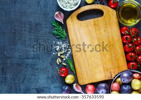 Empty vintage cutting board with organic ingredients (potatoes, tomatoes, garlic and olive oil) over dark grunge background, top view. Raw vegetables from garden for healthy cooking. - stock photo