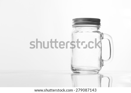 Empty vintage mason Jar  having lid and handle with on White background with reflection and copy space