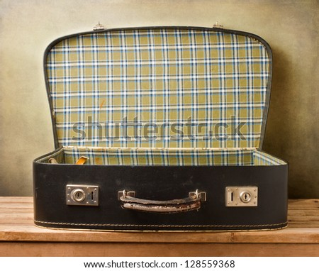 Empty vintage open suitcase on wooden table over grunge background - stock photo