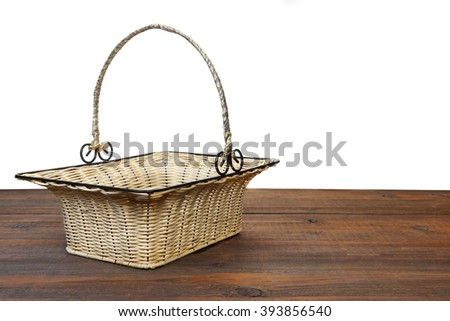 Empty Vintage Wicker Basket With Metal Handle On The Brown Wooden Table Isolated  On White Background - stock photo