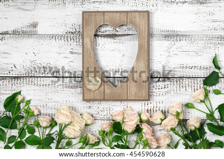 Empty vintage wooden heart shape photo frame with fresh pink roses on rustic white wood background. Top view point, flat lay. - stock photo