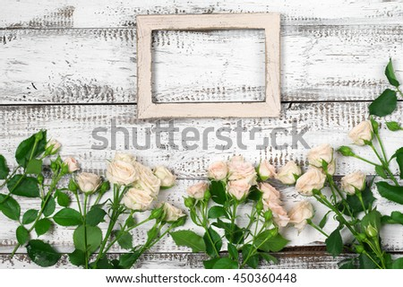 Empty vintage wooden photo frame with fresh pink roses on rustic white wood background. Top view point, flat lay. - stock photo