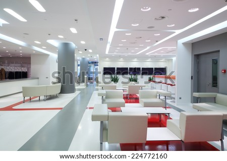 Empty waiting area with white chairs and plasma screens in a modern office  - stock photo