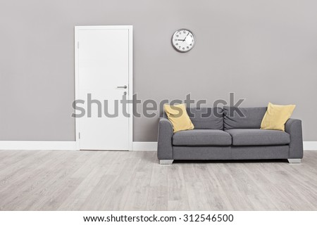 Empty waiting room with a modern gray sofa in front of the door and a clock on the wall - stock photo