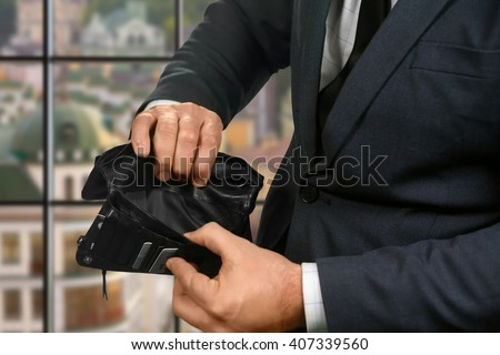 Empty wallet in businessman's hands. Empty wallet on urban background. Waiting for salary. Truly sad situation. - stock photo