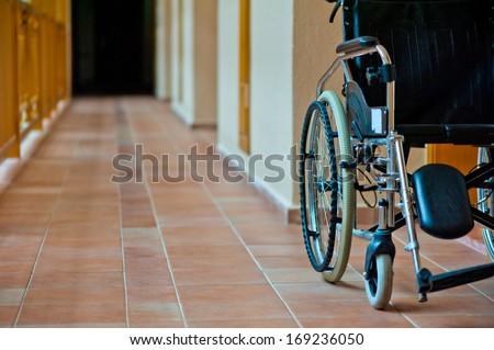 empty wheelchair in hospital corridor - stock photo