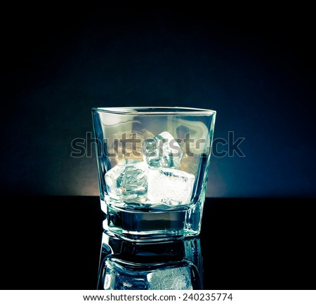 empty whiskey glass with ice and light tint blue disco on black background, with reflection - stock photo