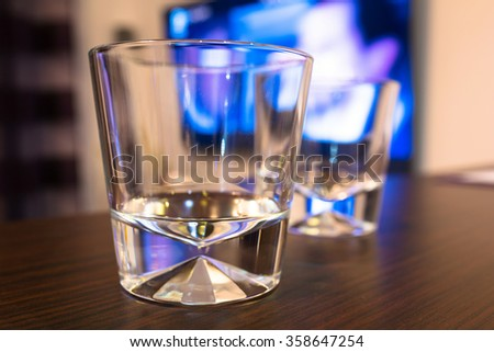 Empty whiskey glasses at the tv - stock photo
