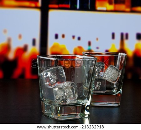 empty whiskey glasses with ice on bar table lounge bar concept - stock photo