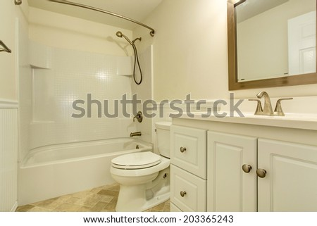 Empty white bathroom with white vanity cabinet and mirror