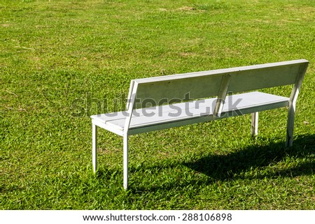 Empty white bench on the lawn in sunny day