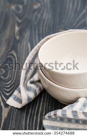 Empty white bowls wrapped with napkin on blue wooden background with copy space - stock photo