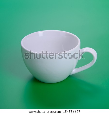 empty white cup on green background
