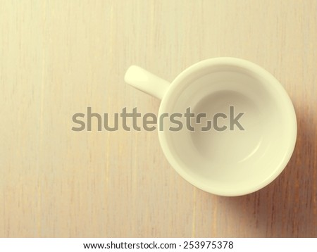 Empty white cup on wood texture background - stock photo
