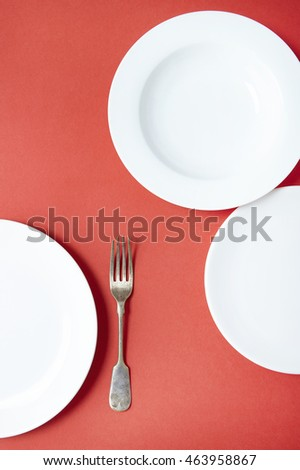 Empty white dinner plates and a fork on a red background