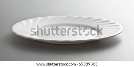empty white dish, grey background - stock photo