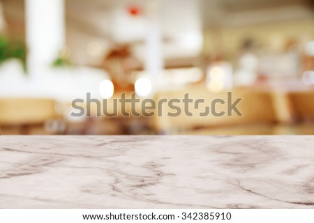 Empty white marble table with blur cafe background. - stock photo