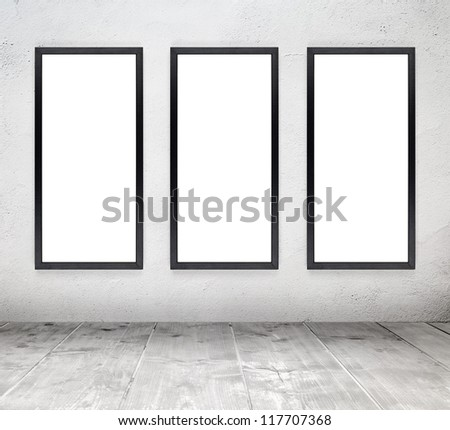 Empty white old interior room with painted concrete wall and empty black wood frames and wooden plank floor - stock photo