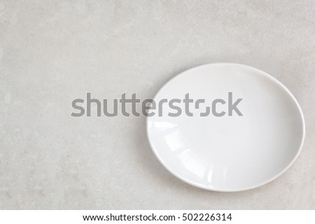 Empty white oval plate on marble.  Top view.
