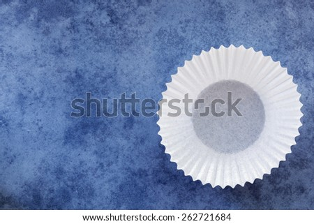 Empty white paper cupcake case over textured blue background.  Overhead view. - stock photo